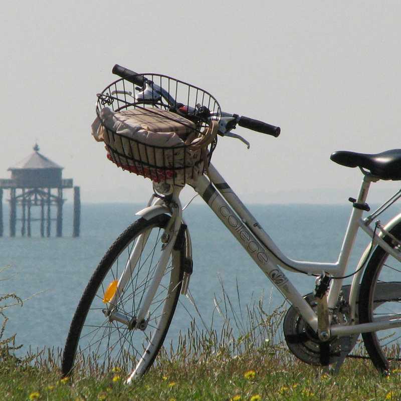 Vélo au premier plan avec en arrière-plan la mer, un voilier et le phare du bout du monde près de La Rochelle