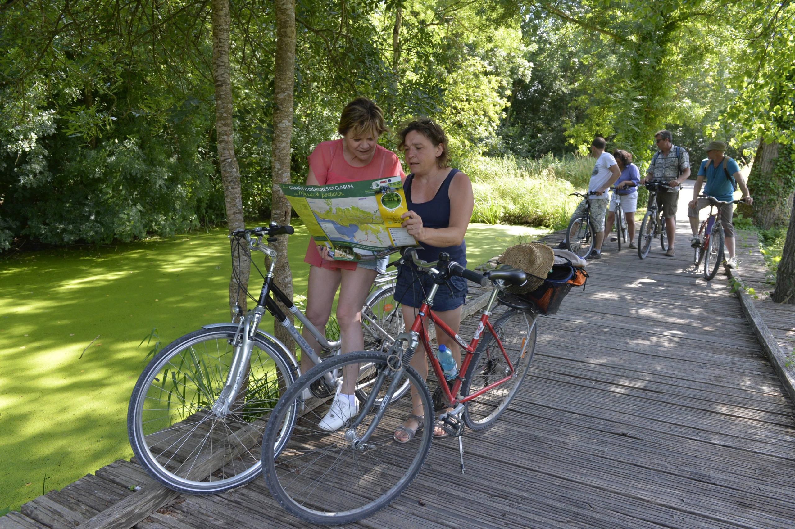 Cyclistes sur une passerelle en bois à La Garette dans le Parc naturel régional du Marais poitevin