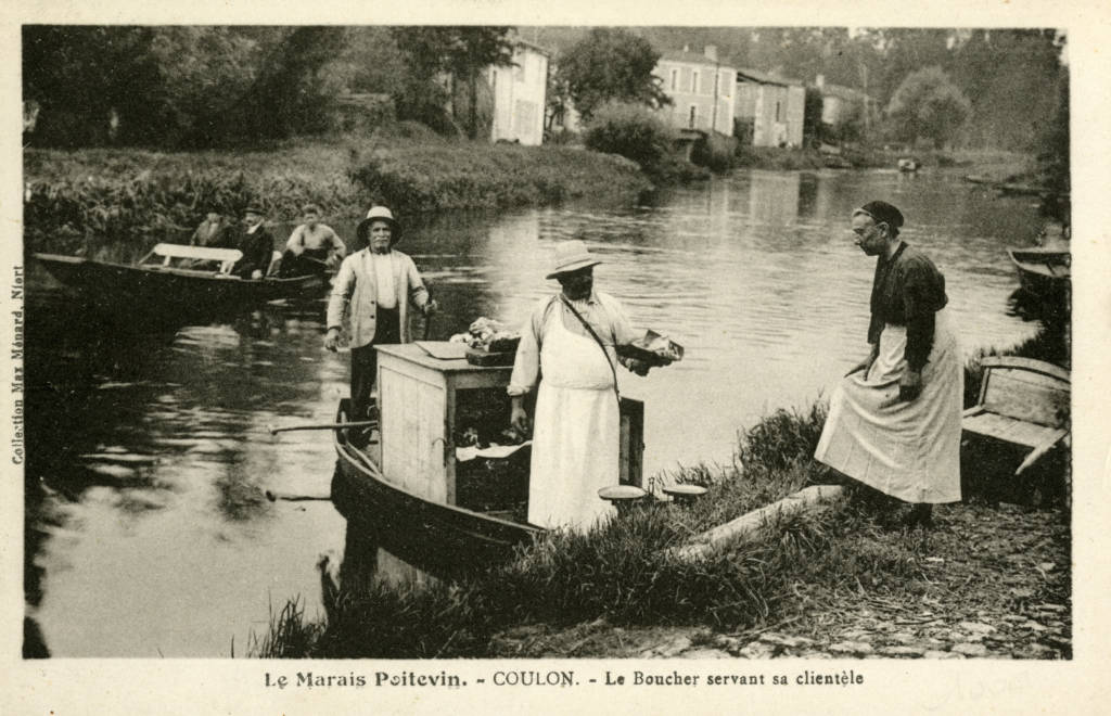 the butcher in boat on the Sèvre niortaise serving his customers in Coulon (coll. Max Menard Niort) in the Natural Regional Park of the Marais poitevin