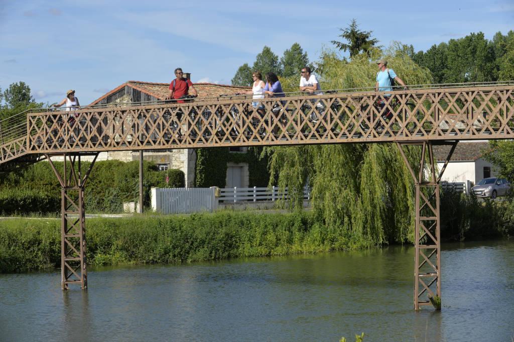 Touristes à vélo sur la passerelle de la Sèvre dans le Marais poitevin
