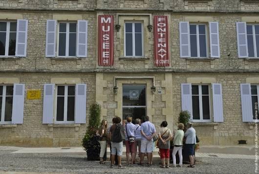 Groupe de personnes devant le Musée de la ville de Fontenay-le-Comte dans le marais poitevin - conservation et la mise en valeur du patrimoine de la ville